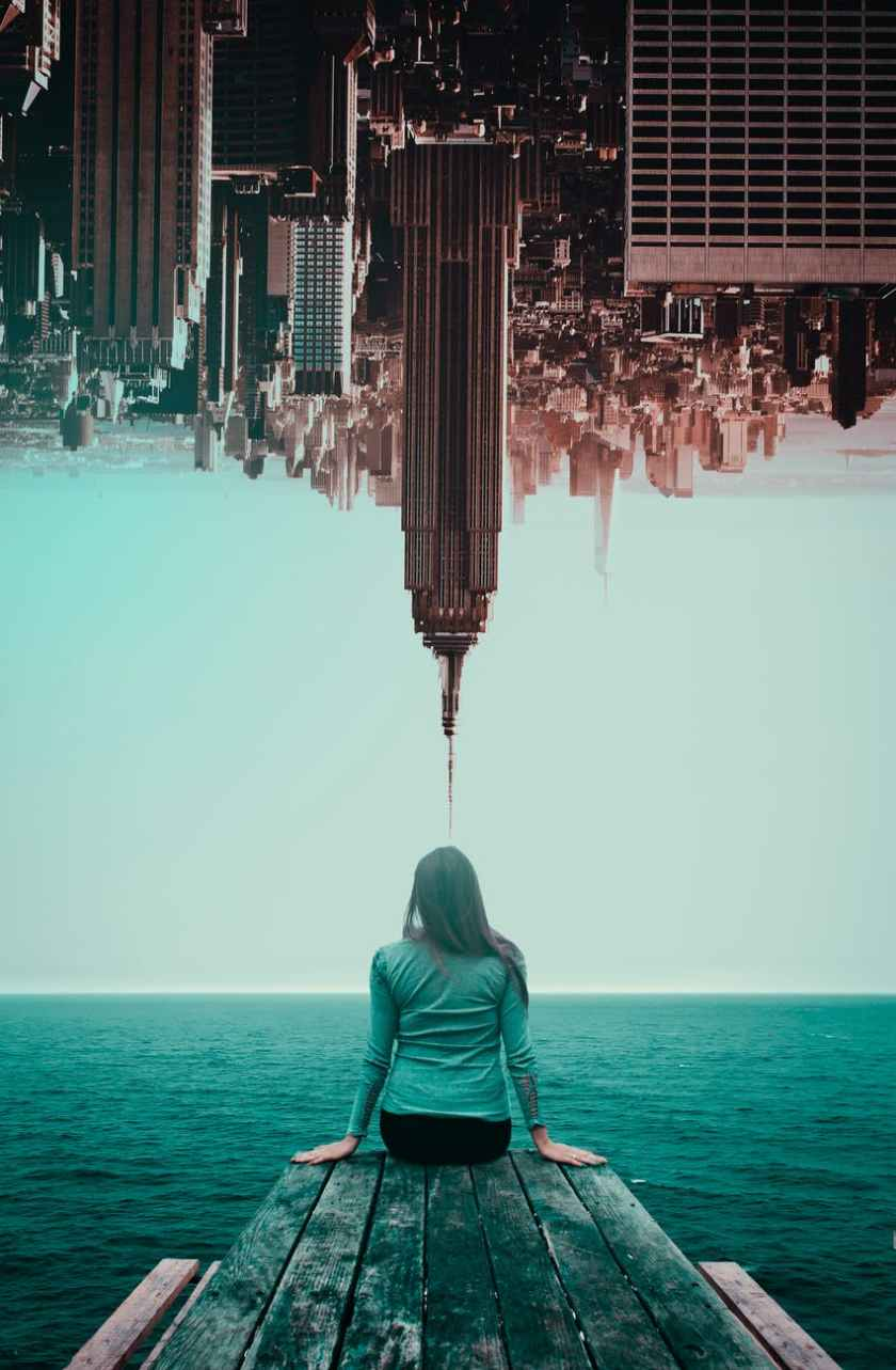 photo of woman and inverted buildings